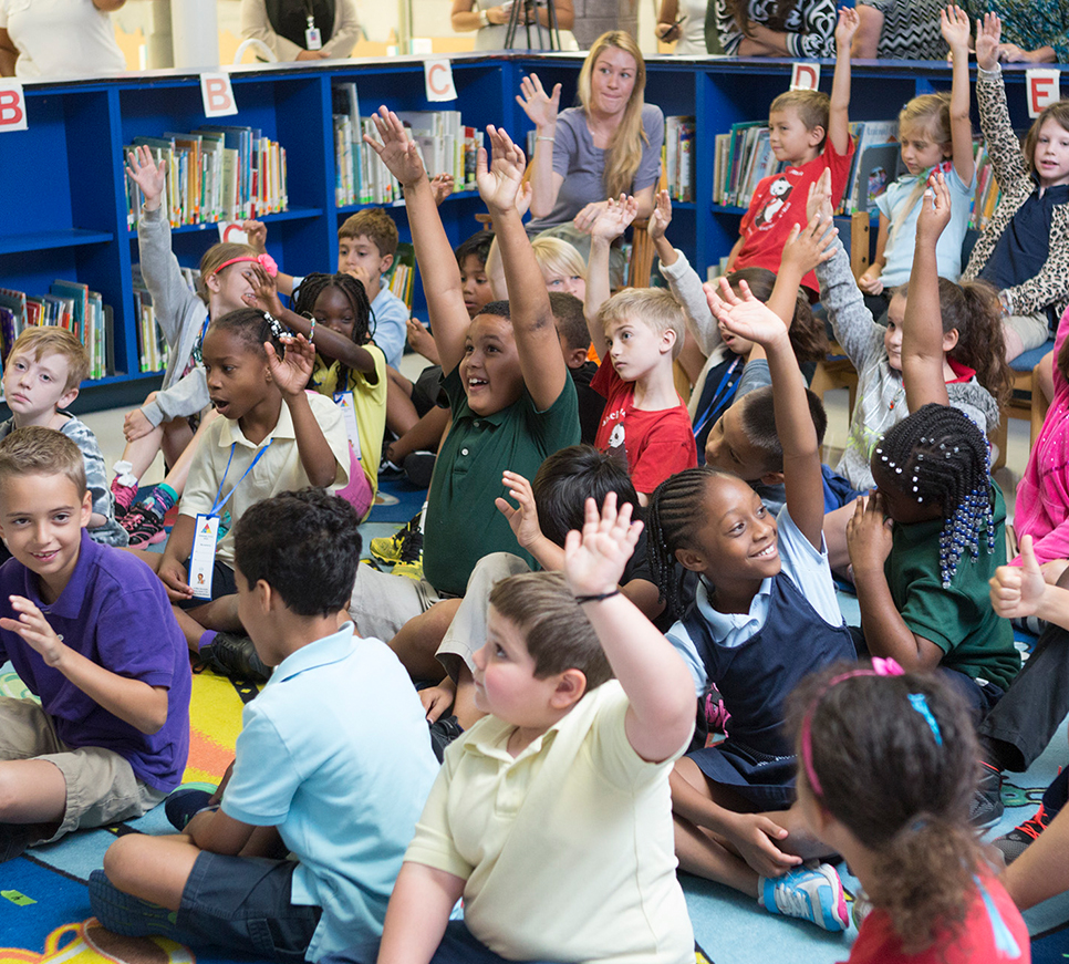Classroom with students raising hands.