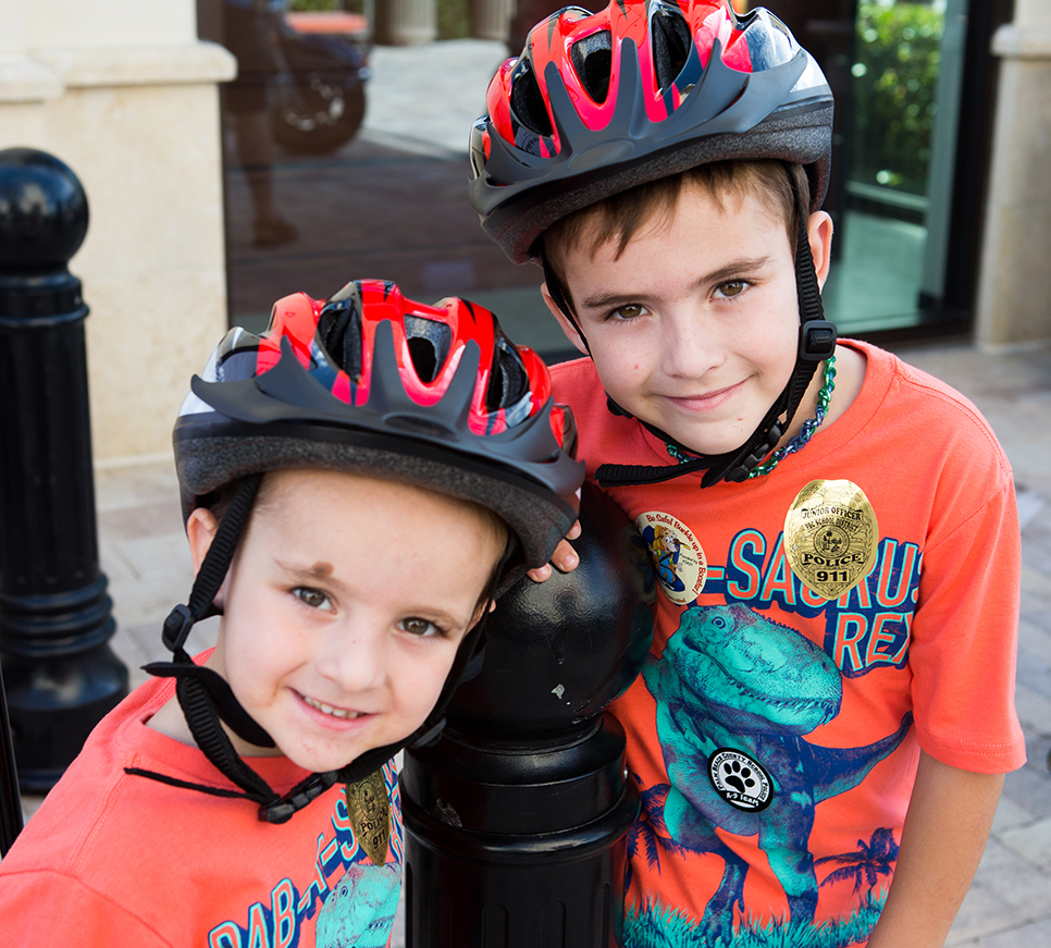 Two young boys with helmets on.