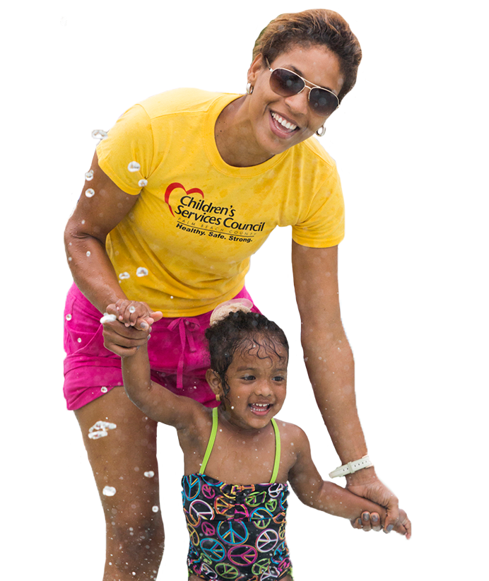 Mother with daughter splashing in pool.