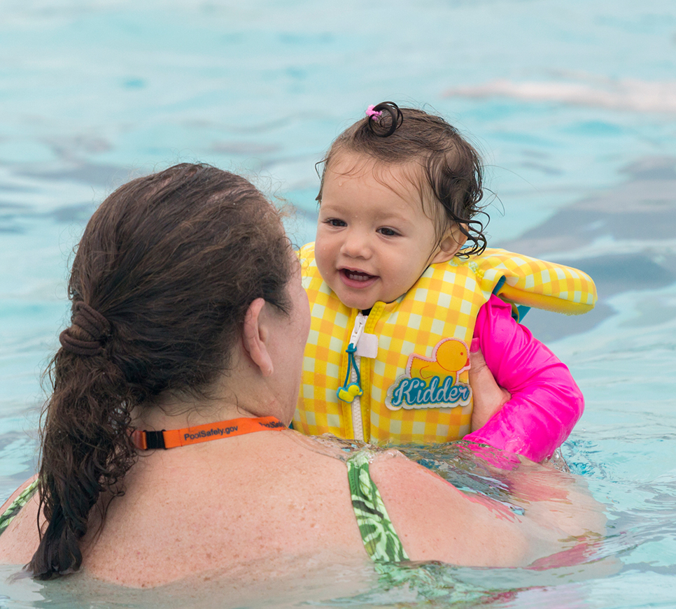 Young girl swimming with mom in pool.