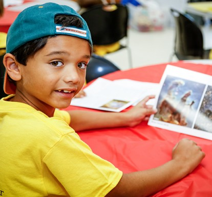 Boy in a CSC T-shirt sits at a table reading a book during a summer camp program.