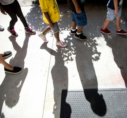 Young children's feet walking in a line outside at a child care center.