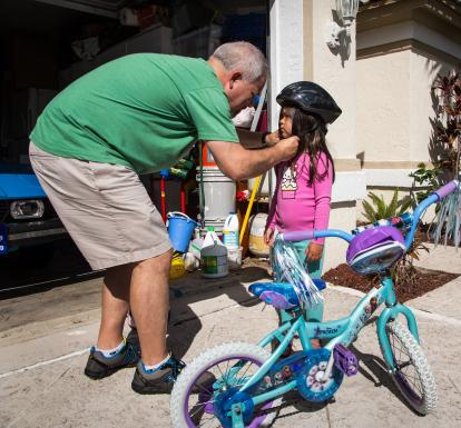 Dad fitting young daughter's bike helmet outside
