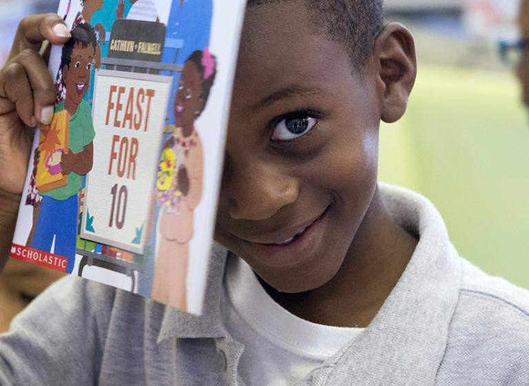 Little boy smiling holding up a book.