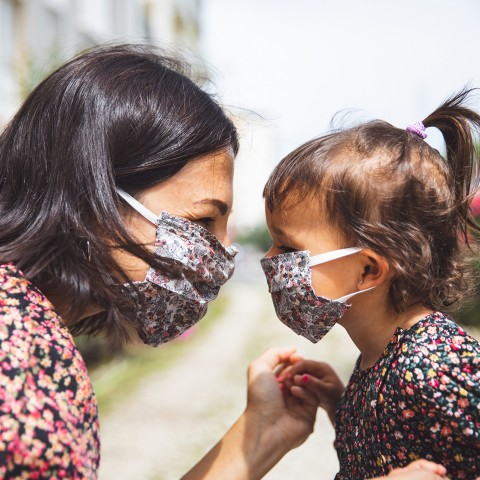Mother and daughter looking eye-to-eye wearing masks