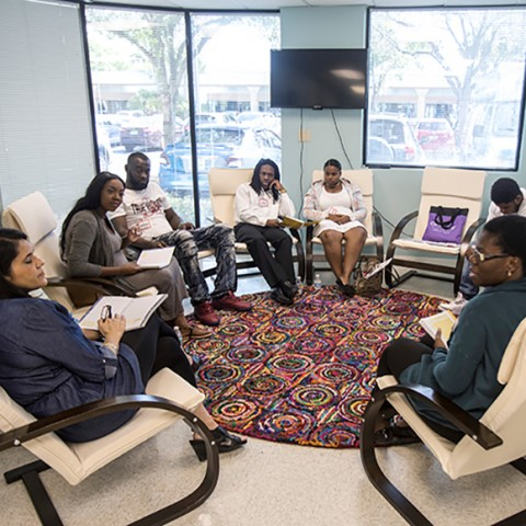 Pregnant women and their partners sit in a circle discussing their health and emotional needs as part of the CenteringPregnancy group prenatal care program in Palm Beach County, FL.