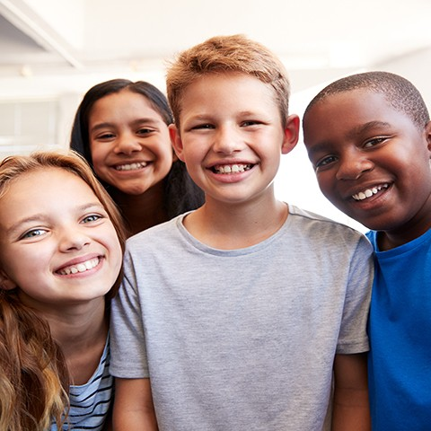 Group of diverse school-age children smiling.