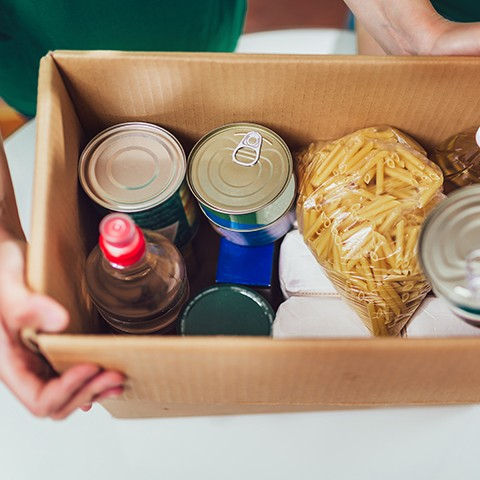A cardboard box of cans and pasta being handed over to someone in need.