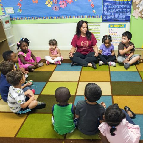 Child care teachers and children sitting in a circle