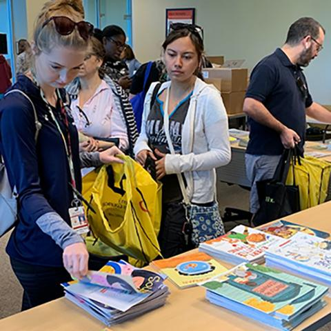 A room full of Palm Beach County public school teachers choose books laid out on a table for Booksgiving.