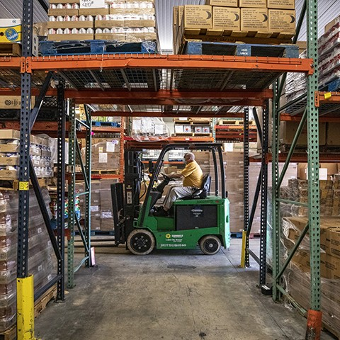 Man on a forklift in the Palm Beach County Food Bank's warehouse, which has shelves filled with boxes and cans of food