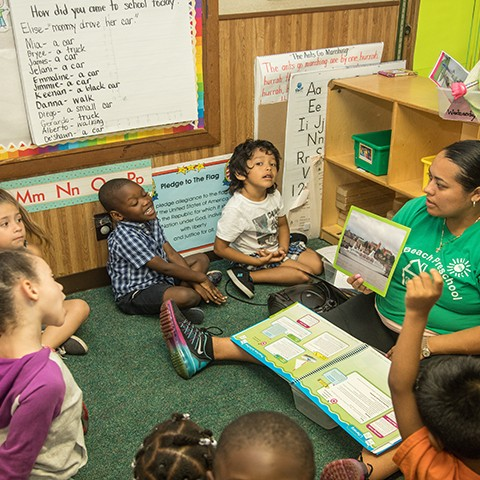 Preschool teacher in a classroom reads a book to young children sitting in a circle. One girl stands, one boy raises his hand.