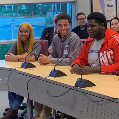 Three high school students from the Student Aces program smile while they sit at a conference table presenting their grant-making project to Children's Services Council's board.